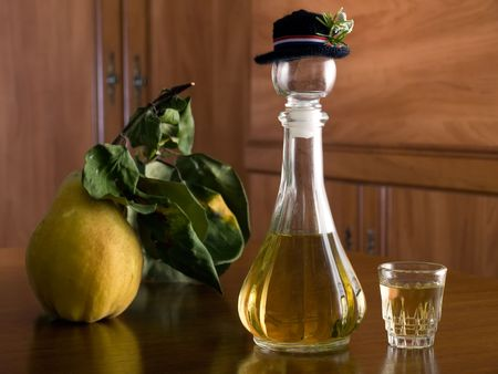 Wooden table with a bottle of brandy and ripe yellow quince on it. photo
