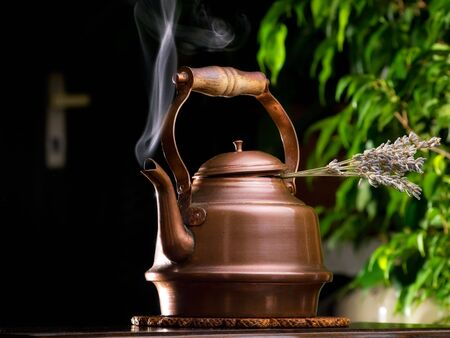 Hot lavender tea in a copper teapot on the table. Stock Photo