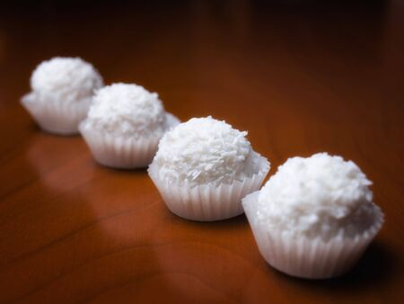 cooky: Delicious coconut balls  sorted on a wooden background.