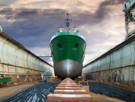 chantier naval: Exp�dier en cale s�che pendant la r�vision, sous un ciel dramatique.  Banque d'images