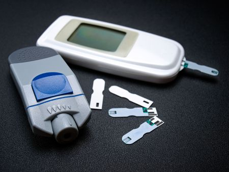glucometer: Glucometer or diabetic testing kit on a dark background.