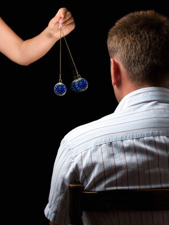 Woman hypnotizes man with a swinging watch during  hypnotic treatment.
