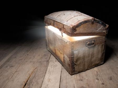 Viejo cofre del Tesoro de madera con fuerte resplandor desde dentro.  Foto de archivo