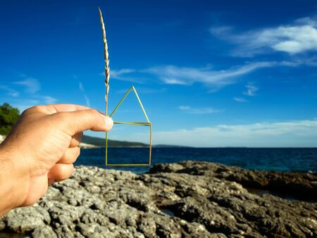 Planning of the construction of a house on the coast , House outline is  made of grass straw. Stock Photo