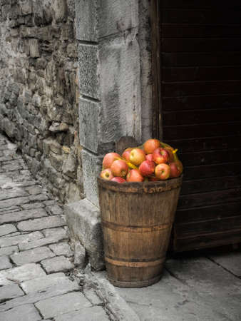 Ripe apple in the basket by the door on a stone street ... photo