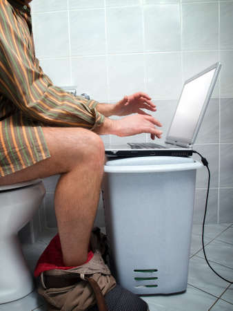 Conceptual view of  an internet addict during calling of nature  in the toilet. Stock Photo