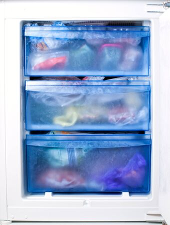 foodstuff: View of the inside of a freezer full of various frozen foodstuff.