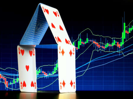 House of cards with a stock graph in the background represent mortgage themes... photo