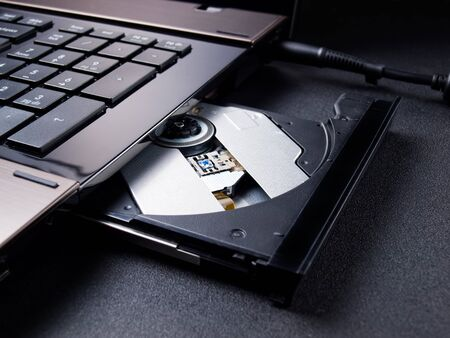 portable rom: Open optical disc drive on a modern laptop computer without disc. Stock Photo