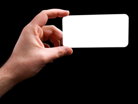 Human hand is holding a blank white card isolated on a black background. Stock Photo - 9106988