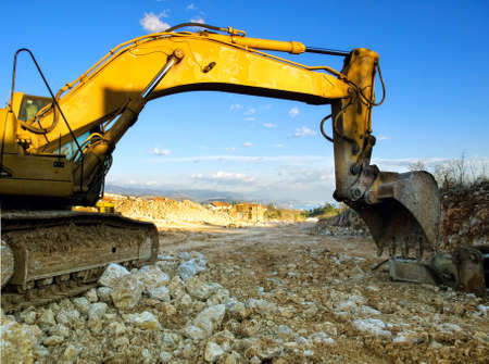 Digger machine at the construction site under blue sky... Stock Photo - 9106986