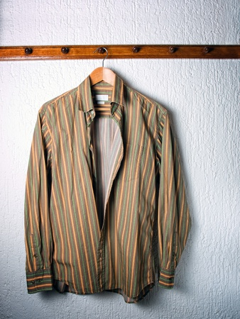 shirts on hangers: Only one striped shirt on a hanger in the wardrobe. Stock Photo