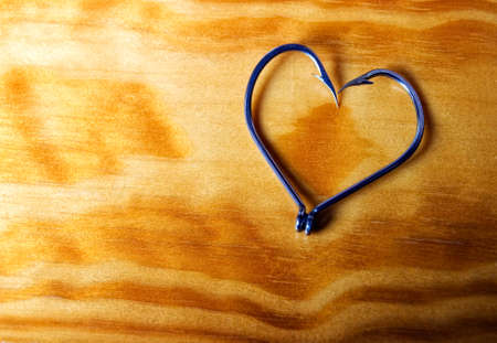 Heart symbol made from fishhooks on a wooden background. photo