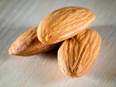 Closeup view of three almonds on a wooden background. Stock Photo