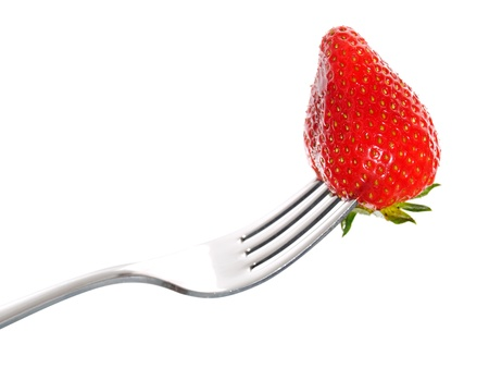 Strawberry on a fork isolated on white background.