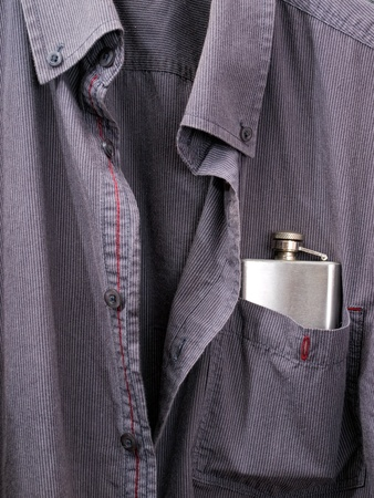 boozer: Conceptual view of alcoholism presented with a hip flask in a shirt pocket.
