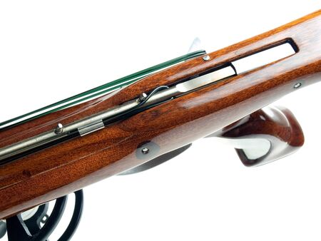 speargun: Closeup view of wooden speargun and trigger mechanism on a white background.