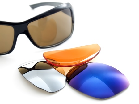 Sunglasses and few optical UV filters on a white background.