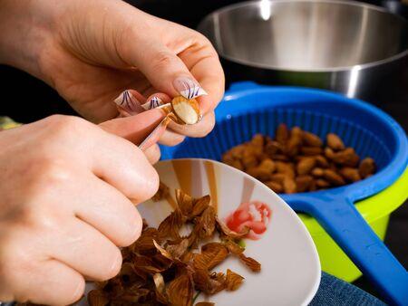 Women is peeling foreskin from almond kernels... 版權商用圖片