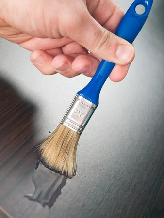 Closeup view of painting or varnishing wood. photo