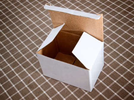 An empty cardboard box on a checked background photo