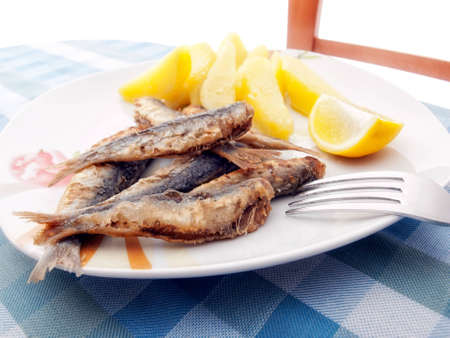 Fresh fried sardines with boiled potatoes and a slice of lemon  photo
