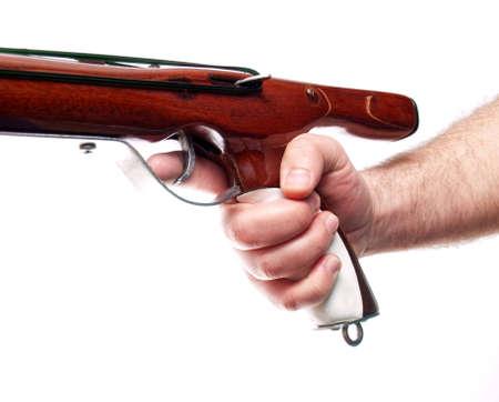 finger on trigger: Finger on the speargun trigger on a white background.