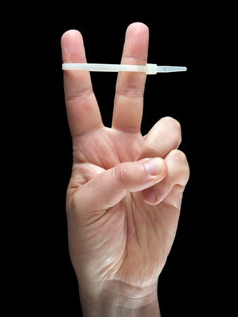zip tie: Hand is showing a victory sign with a zip tie on fingers on a black background