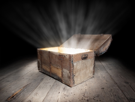 Ancient wooden treasure chest with the strong glow from inside   Stock Photo