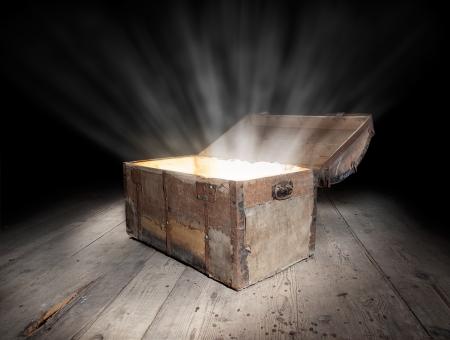 En el pecho del tesoro antiguo de madera con la luz fuerte desde el interior