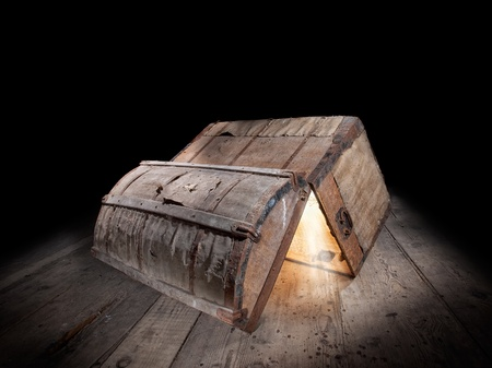 Upturned and opened an old wooden box with glowing light from inside    photo