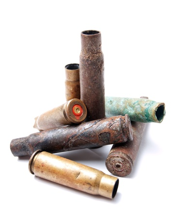 spent: Lot of various old bullet cartridges on a white background
