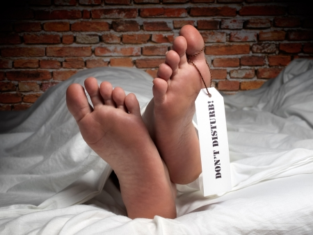 morgue: Funny image of a man who is resting covered with a sheet like in the morgue, with a label on his thumb  Stock Photo