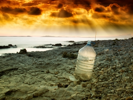 Last bottle of collected fresh water on the coast near the sea. photo