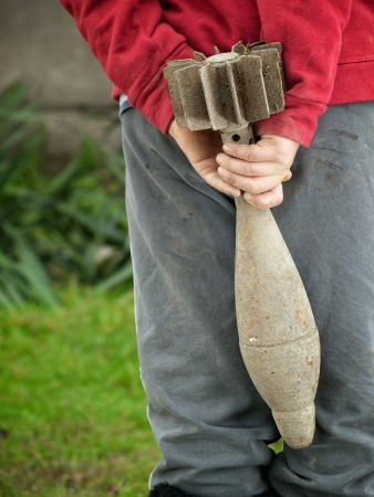 artillery shell: Little boy is playing with an unexploded mortar shell somewhere in a war zone.