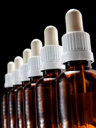 goteros: Varias botellas de cristal con cuentagotas en una fila en fondo negro Foto de archivo