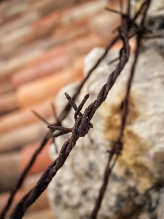 Rusty barbed wire above roof and stone wall. photo