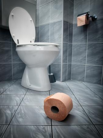 Kijkje op het wc-papier op de vloer en het toilet op de achtergrond