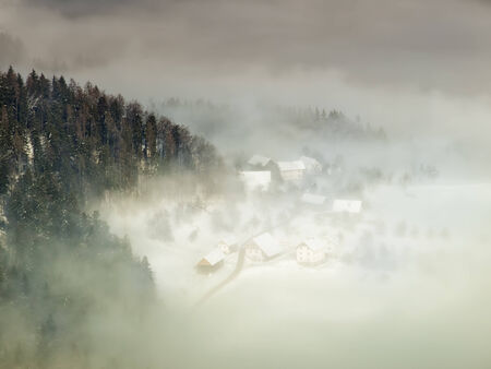 View from the mountain to the alpine village in the mist  photo