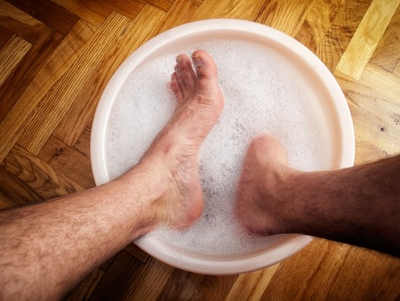 drench: Man soaking his feet in a washbowl.
