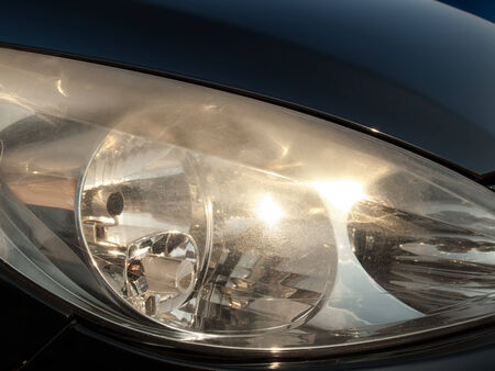 dense mats: Damaged and blurred headlight surface as a result of weather condition and aging of a car.