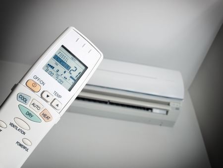 cold air: Remote control with two choices of energy source and with an air condition device in the background.