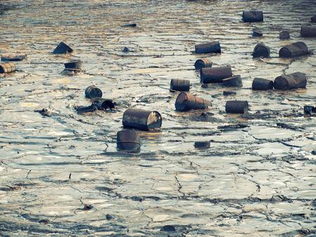 contaminacion del agua: barriles de estaño están flotando sobre una superficie de agua e hidrocarburos.