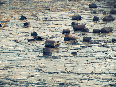 Tin barrels are floating on a oily water surface.