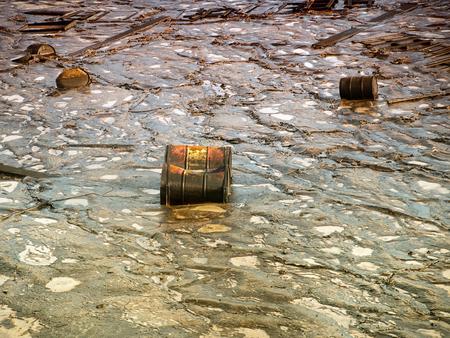 contaminacion del agua: barriles metálicos industriales viejos rodeados de un ambiente contaminado. Foto de archivo