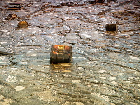 pollutant: Old industrial metal barrels surrounded by contaminated environment. Stock Photo
