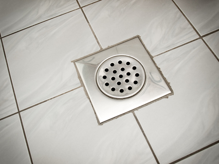 Drain on the floor of a bathroom or a kitchen.