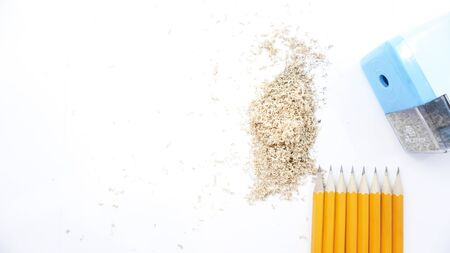 sharpened pencils and sharpener are on a white background