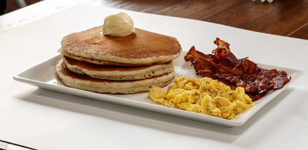 three pancakes with bacon and scrambled eggs