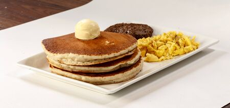 three pancakes with sausage and scrambled eggs Фото со стока